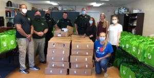 SWAG board members, interns, and members of the Alachua County Sherriff's Office standing next to boxes of food