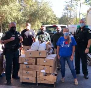 SWAG board chair Dorothy Benson and members of the Alachua County Sherriff's Office standing next to boxes of food