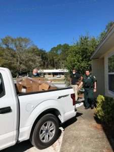 Members of the Alachua County Sherriff's Office load boxes of food into a truck to distribute to the SWAG community