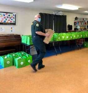 A member of the Alachua County Sherriff's Office carries a box of food past a row of already-filled tote bags