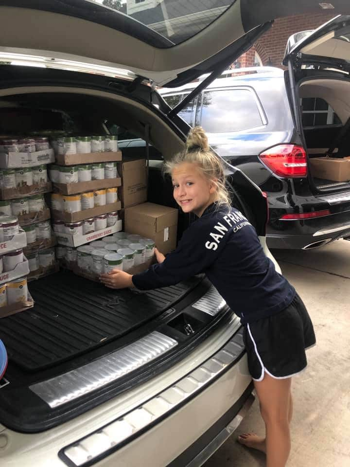 Young volunteers unloading boxes from a car