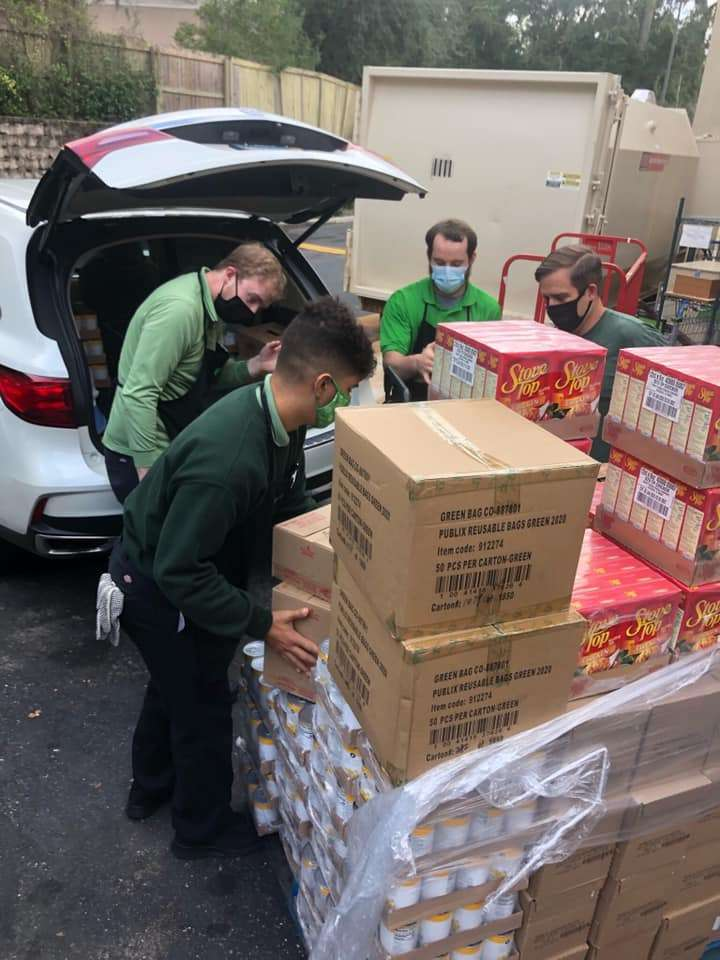 Publix employees help load boxes of food into a car