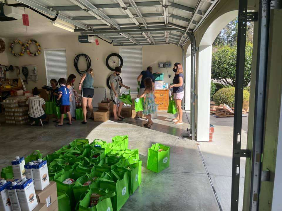 Families working together to tote bags with food