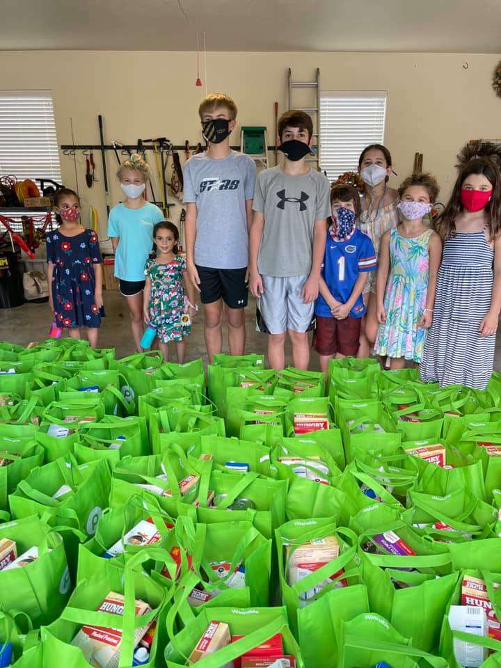 A group of children stand behind a large group of tote bags filled with sides and trimmings for 2020 turkey distribution