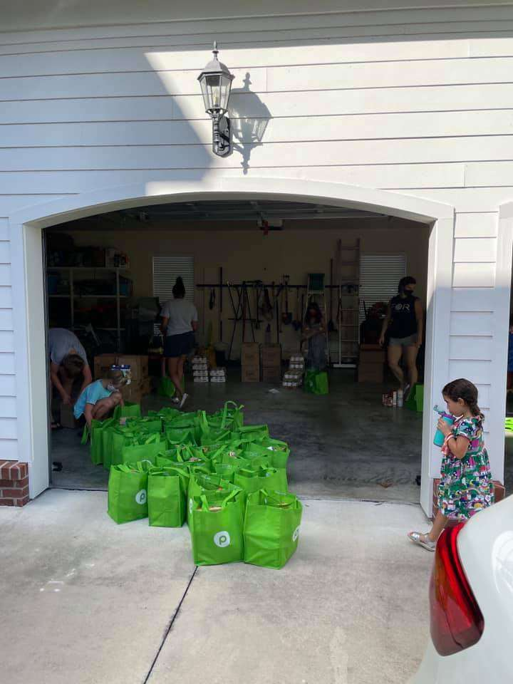 A garage overflowing with tote bags filled with food for 200 SWAG families