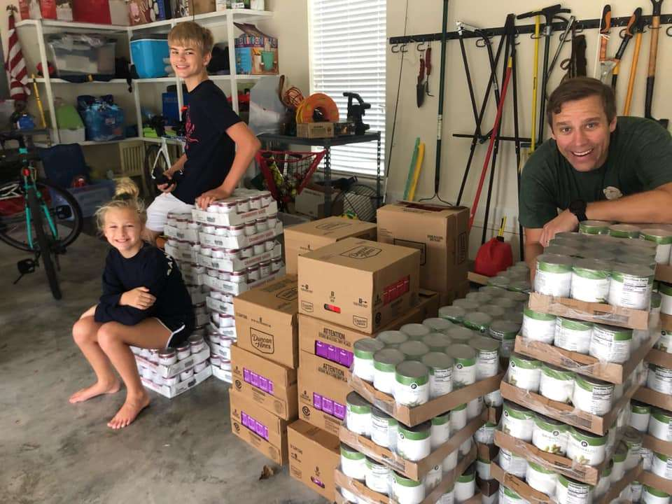 Volunteers standing with large stacks of canned food for the 2020 turkey distribution from SWAG