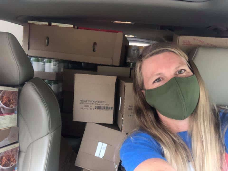 SWAG board member Dorothy Thomas driving a car stuffed with boxes of food to prepare for turkey distribution