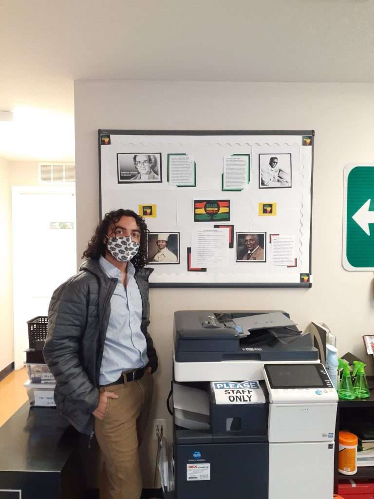 SWAG intern Cyrus Santiago standing next to a community bulletin board for Black History Month