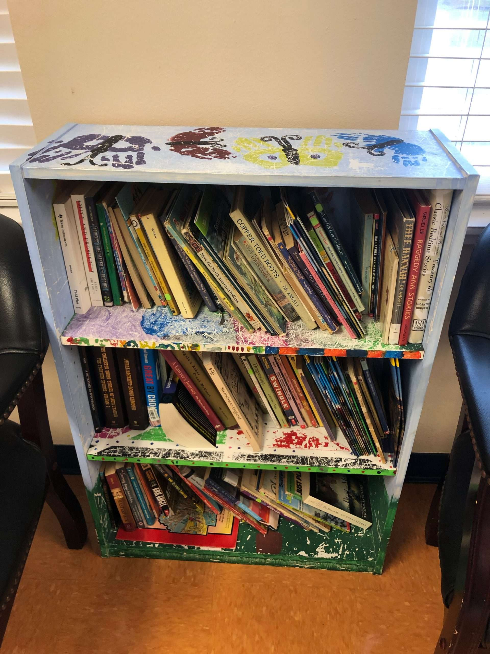A colorful shelf with children's books inside the SWAG Family Resource Center