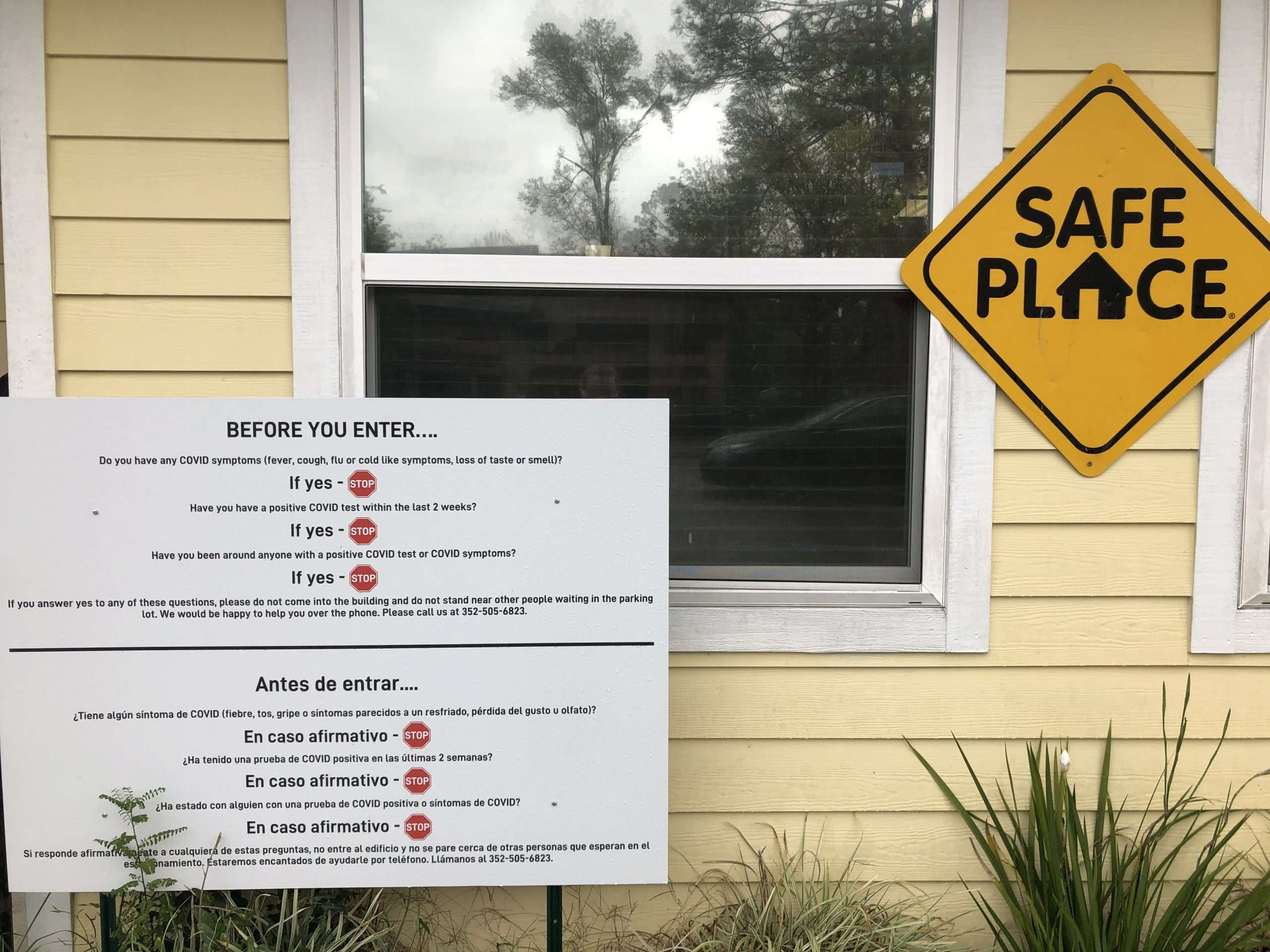 Signage in front of the building listing COVID precautions