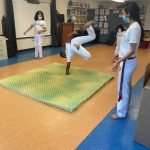 A Capoeira student standing upside-down on one hand during a special cord promotion ceremony at the SWAG FRC
