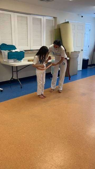 A Capoeira student receives a belt promotion at a special ceremony in the SWAG Family Resource Center