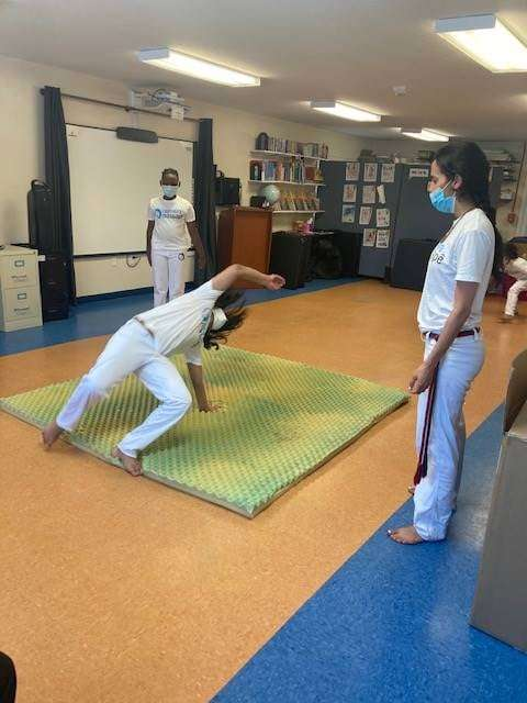 A student practices Capoeira on a mat in the SWAG Family Resource Center, surrounded by classmates and instructor Ms. Doce