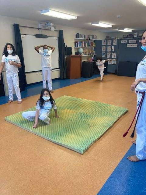 A student practices Capoeira on a mat in the SWAG Family Resource Center, surrounded by classmates
