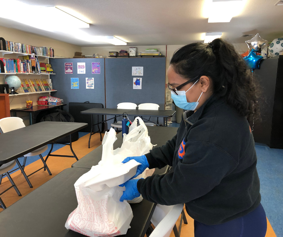 Board member Mona Sayedul Huq preparing a grab-and-go meal bag for distribution during the April 2021 Community Dinner
