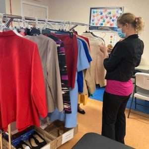An employability workshop participant browses through professional clothing at the SWAG Family Resource Center