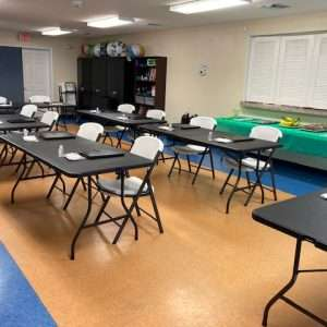Chairs and tables arranged in rows with packets for participants in the April 2021 employability workshop