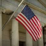 An American flag waving in front of a building adorned with columns