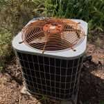 An outdoor HVAC unit with a rusty grill