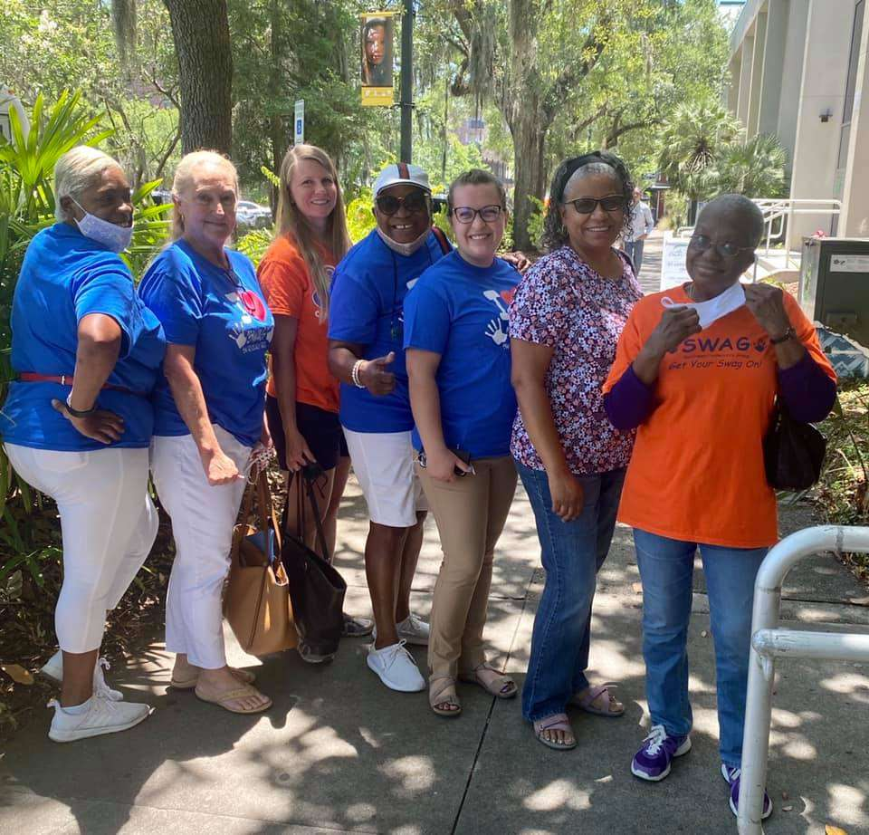 SWAG members, friends, and family of Joan Canton stand outside the County Commission building in May 2021