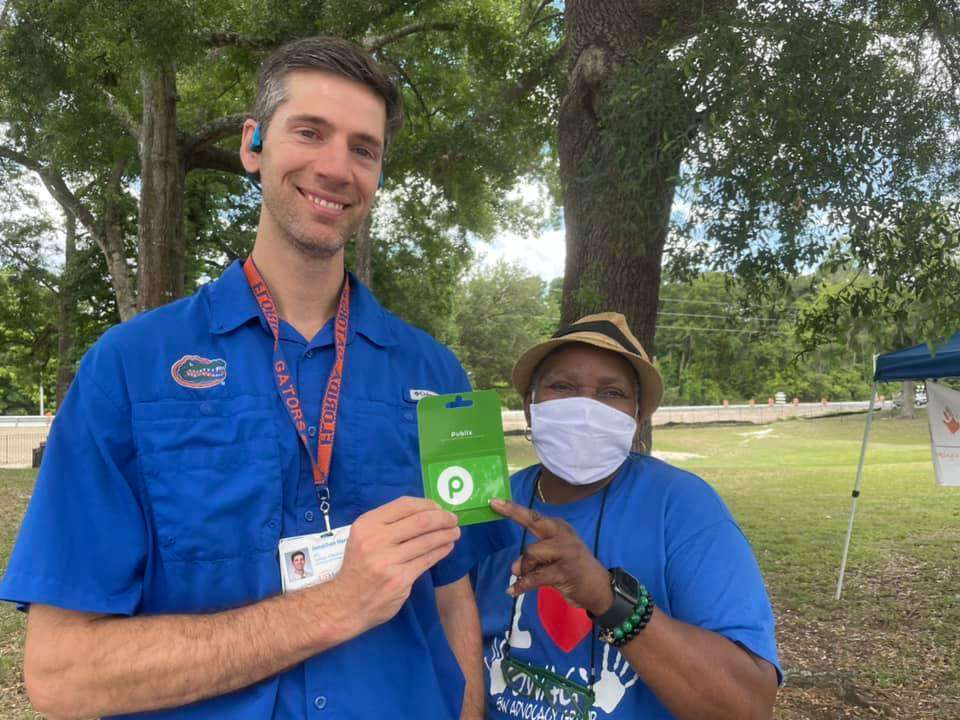 SWAG board member McLinda Gilchrist and Dr. Grant Harrell of the UF Mobile Outreach Clinic hold a $20 Publix gift card