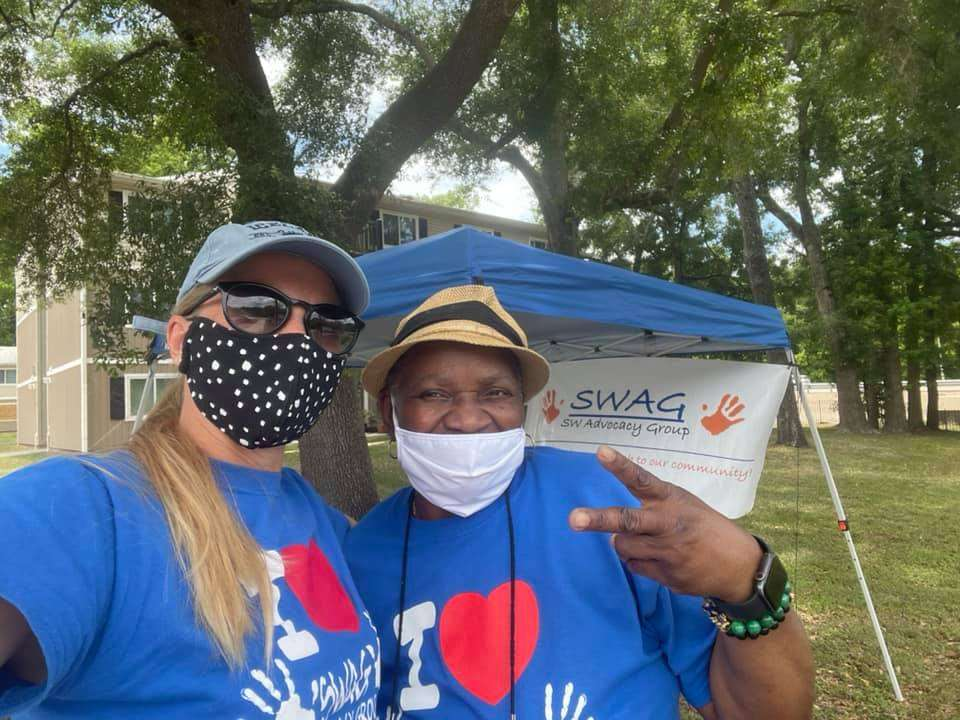 SWAG board members McLinda Gilchrist and Dorothy Thomas stand together in front of a vaccine distribution tent