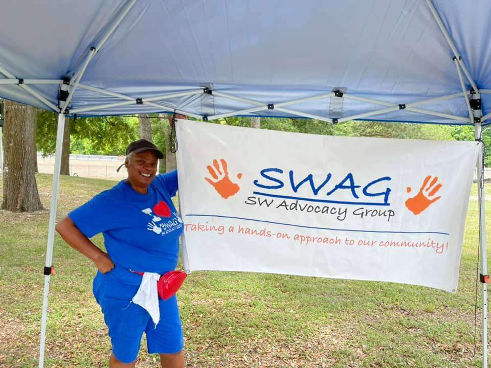 Samantha Kimbrough wears a SWAG shirt and stands next to a SWAG banner at a vaccine distribution event in May 2021