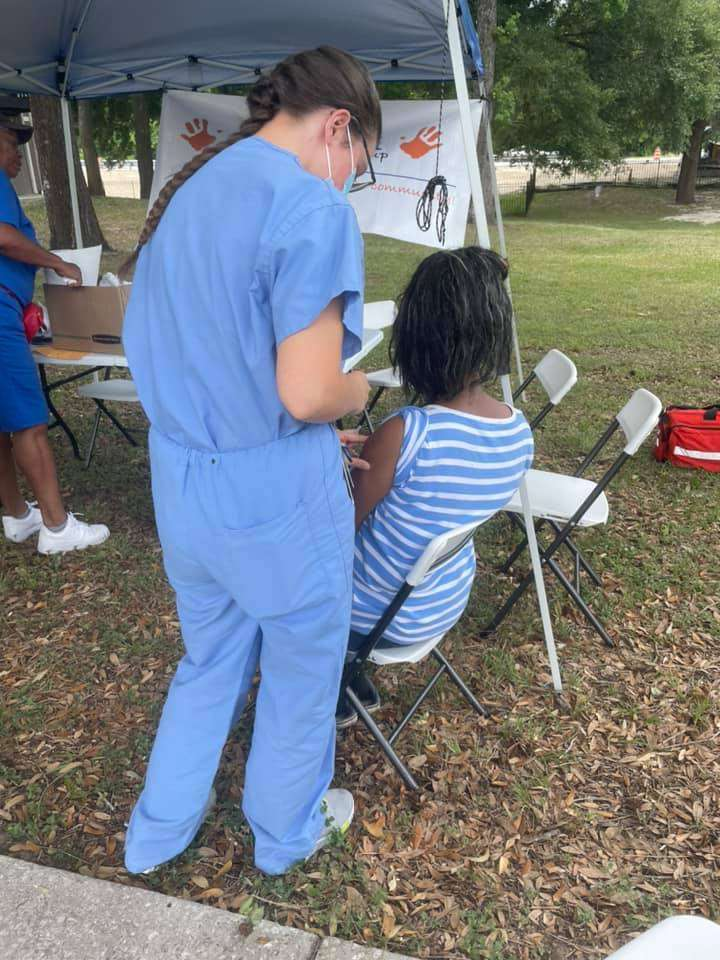 A Majestic Oaks community member receives a vaccine from a UF medical student volunteer during a May 2021 distribution event