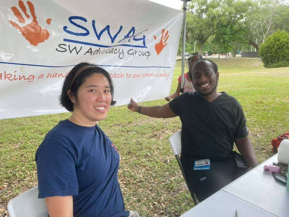UF medical student volunteers sit in front of a SWAG banner during a COVID-19 vaccination event in Majestic Oaks