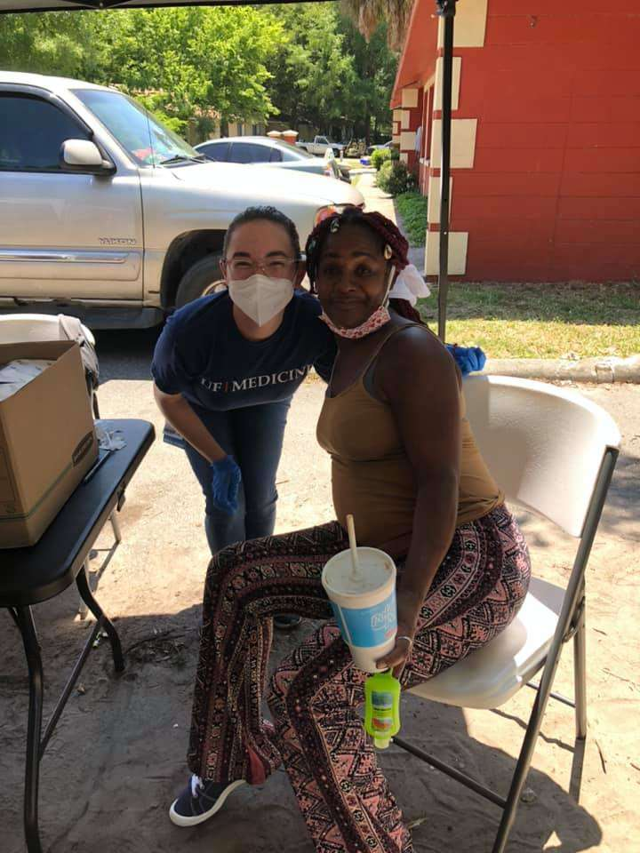 A UF medical student volunteer and a community member who has just received a vaccine smile together for the camera