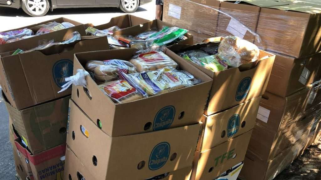 Boxes of groceries from Bread of the Mighty Food Bank are stacked high in the Tower Oaks Glen neighborhood