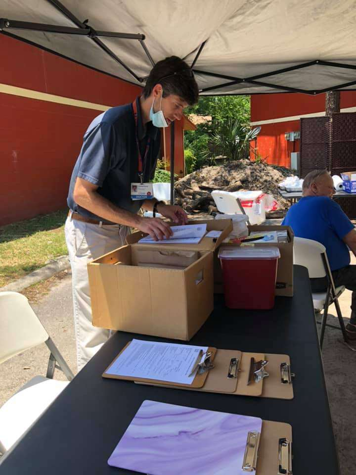 Dr. Grant Harrell of UF's Mobile Outreach Clinic arranges medical forms in a vaccination booth in Tower Oaks Glen
