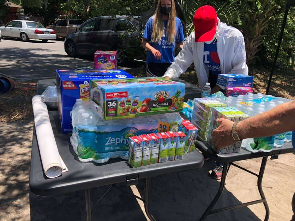 Juice boxes and snacks are piled high on an outdoor table to be given away to people receiving vaccines in Tower Oaks Glen
