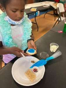 A Homework Help student carefully decorates a cooking with blue and white icing as well as rainbow sprinkles