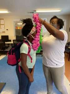 A SWAG Family Resource Center staff member drapes pink and green leis around a Homework Help student's neck