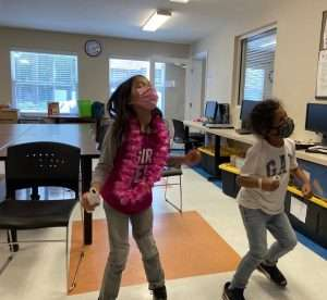 Two Homework Help students move around while playing a Wii game in the SWAG Family Resource Center