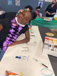 A smiling Homework Help student wearing a purple lei leans casually against a table with a drawing she has made