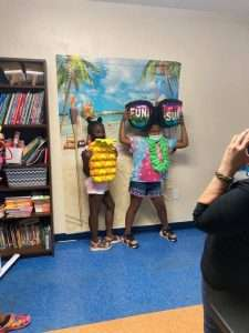 Two Homework Help students pose in front of a summer-themed photo booth, holding fun props such as inflatable sunglasses