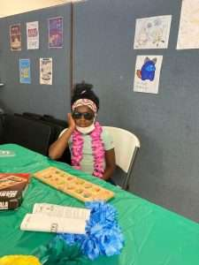 A Homework Help student poses for the camera wearing sunglasses and a pink lei during the June 2021 end-of-year celebration