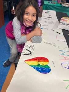 """A Homework Help student smiles for the camera next to a drawing of a rainbow-colored heart saying """"I love SWAG"""""""