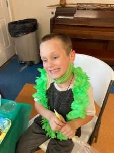A Homework Help student wears a lime-green lei and smiles off into the distance