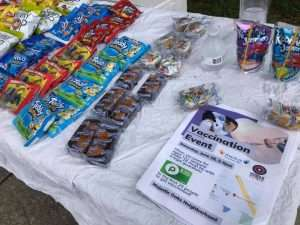 Free snacks and flyers for the June 2021 vaccination event in Majestic Oaks are laid out on an outdoor table