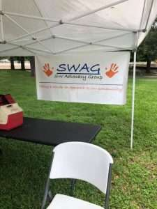 A SWAG sign hangs on a tent in the Majestic Oaks neighborhood during a COVID-19 vaccination event