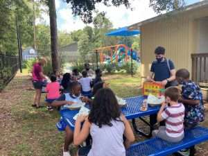 Children sit outdoors around brand-new picnic tables behind the SWAG Family Resource Center