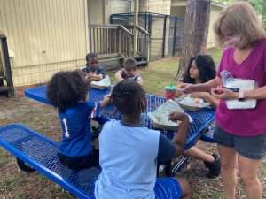 SWAG children eat a meal together at picnic tables that arrived for the Family Resource Center in July 2021