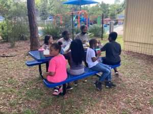 A group of children sit around a blue metal picnic table, with the playground at the SWAG Family Resource in the background