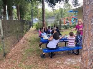 A SWAG volunteer leads children in an activity using the brand-new picnic tables at the Family Resource Center in July 2021