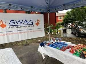 Free snacks are laid out on an outdoor table below a SWAG sign, ready for the June 2021 vaccination event in Tower Oaks