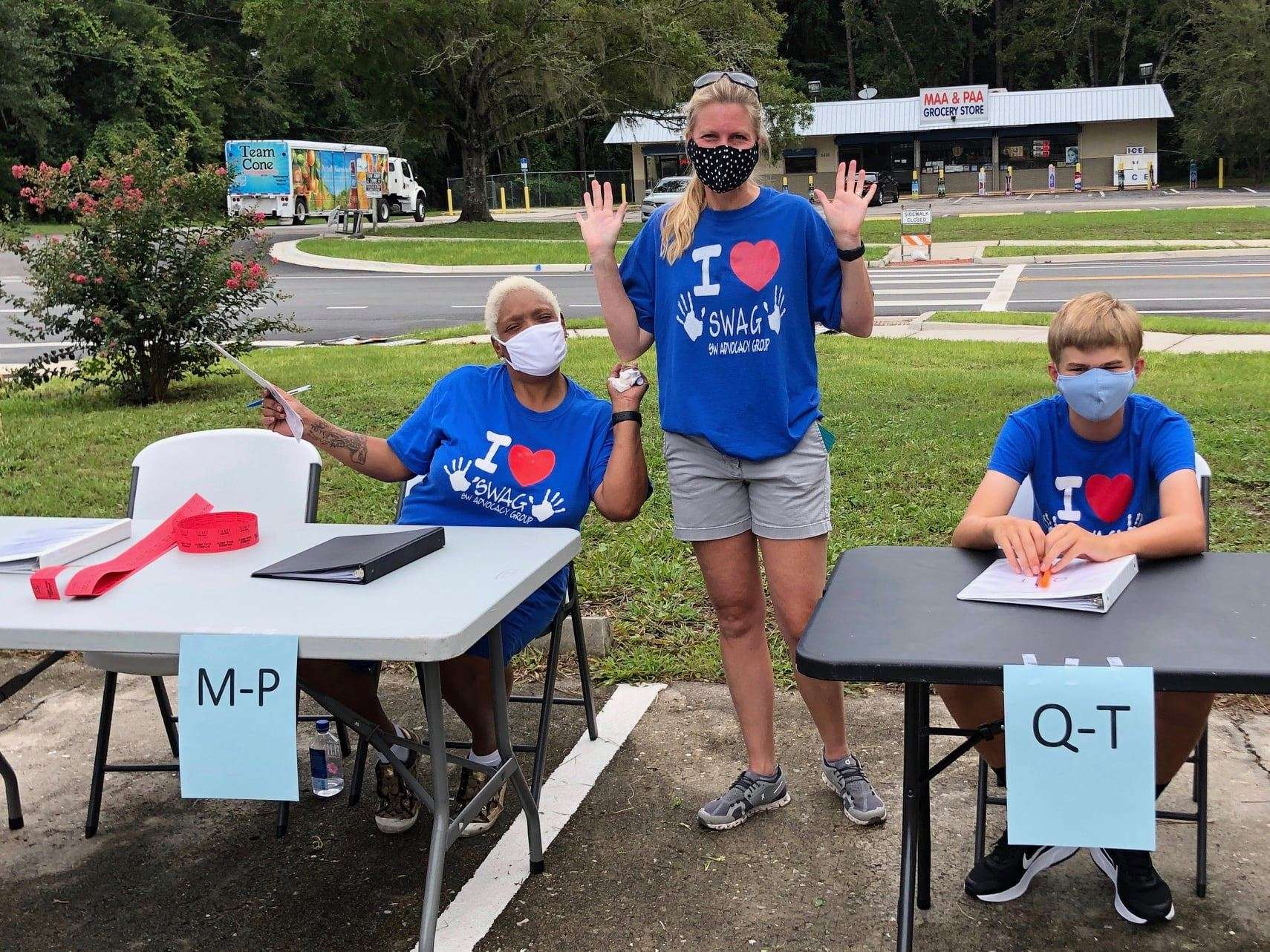 SWAG board members Samantha Gilchrist and Dorothy Thomas, as well as a young helper, staff a back-to-school sign-in table