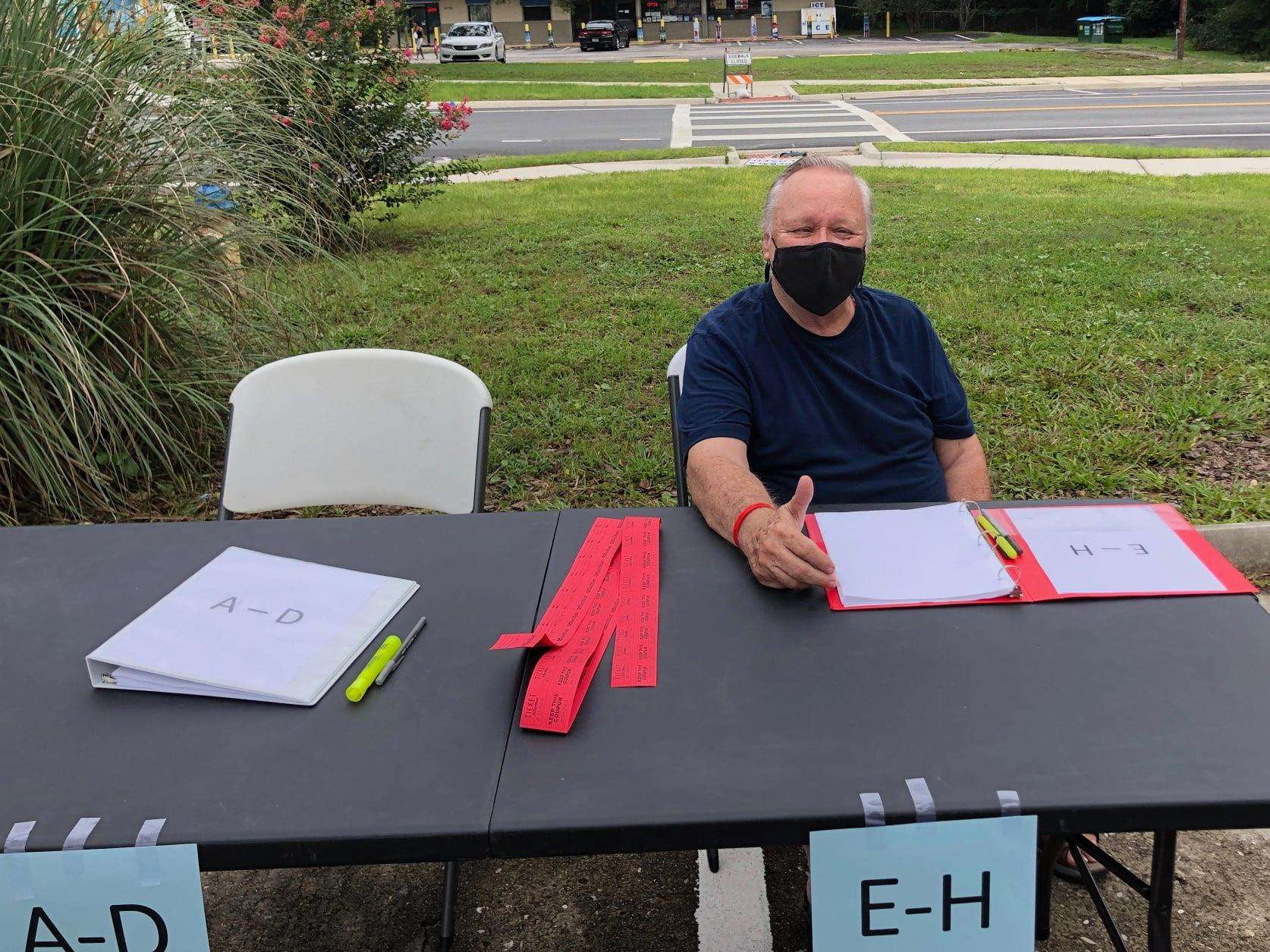 SWAG board member Chuck Clark wears a mask and sits at the back-to-school sign-in table, ready to greet families.